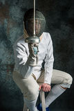 The man wearing fencing suit with sword against gray. The man wearing fencing suit posing with sword against gray studio background Royalty Free Stock Photo