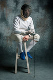 The man wearing fencing suit with sword against gray Stock Image