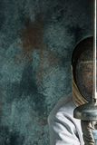 The man wearing fencing suit with sword against gray Royalty Free Stock Images