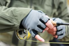 Man wearing fingerless gloves for fly fishing. Man wearing protective warm fingerless gloves for fly fishing in a close up view of his hands on the rod and reel Stock Images