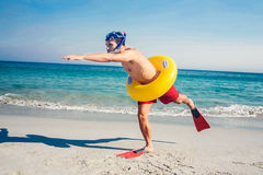 Man wearing flippers and rubber ring at the beach Stock Images