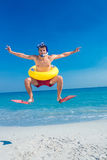 Man wearing flippers and rubber ring at the beach Stock Photos
