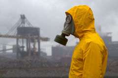 Man wearing a gas mask. Man wearing gas mask standing infront of factory. Side shot. Background out of focus