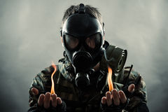 Man wearing gas mask with fire on hands. Military man wearing a gas mask with fire burning in each hand and a smoky background royalty free stock images
