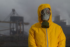 Man wearing gas mask standing infront of factory. Royalty Free Stock Photos