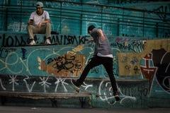 Man Wearing Geay Shirt Playing Skateboard Stock Photography
