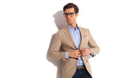 Man wearing glasses while fixing his jacket Stock Photography