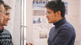 A man wearing glasses and a gray blue sweater actively gesticulating, telling something. He stands in front of the stand with maps and diagrams. Both his hands stock video footage