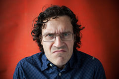 Man wearing glasses with a grimace of displeasure. On red background Royalty Free Stock Photography