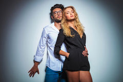 Man wearing glasses holding his blonde woman in black dress. Sexy men wearing glasses leaning against studio background while holding his blonde women in black Stock Photo