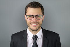 Man wearing glasses. Portrait of a smiling man over a gray background Royalty Free Stock Image