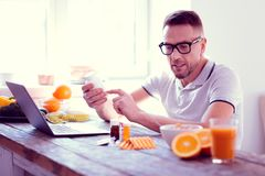 Man wearing glasses reading the information about supplements and vitamins. Supplements and vitamins. Man wearing glasses leading healthy lifestyle reading the stock photography