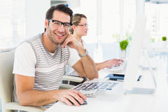 Man wearing glasses sitting at desk looking at camera Royalty Free Stock Photos