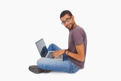 Man wearing glasses sitting on floor using laptop and looking at Royalty Free Stock Images