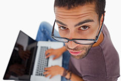 Man wearing glasses sitting on floor using laptop and looking up Stock Images