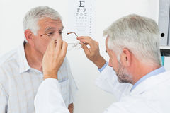 Man wearing glasses after taking vision test at doctor. Senior men wearing glasses after taking a vision test at the doctor Stock Images
