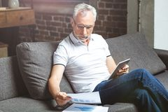 Man wearing glasses using on digital tablet. Senior bearded man wearing glasses using on digital tablet and looking at documents at home royalty free stock image