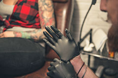 Man wearing gloves before creating picure on female body. Male preparing for work before making images in tattoo salon Royalty Free Stock Photos