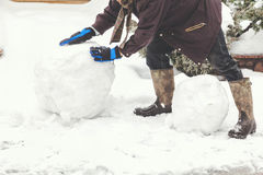 Man wearing gloves rolled large snowball is close lower Stock Photo