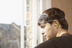 Man Wearing Goggles And Earplugs While Looking Out Of Window Stock Images