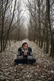Man Wearing Gray Black Zip Hoodie Jacket Praying in Between Black Tree during Daytime Royalty Free Stock Photo
