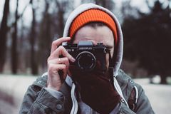 Man Wearing Gray Hooded Jacket Holding Black Camera Royalty Free Stock Photography