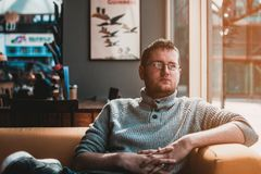 Man Wearing Gray Knitted Sweater Sitting on Brown Fabric Sofa stock photography