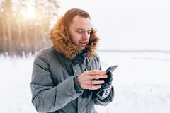 Man wearing gray winter jacket with hood on in winter snow. With Copy free space Royalty Free Stock Photo