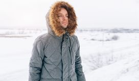 Man wearing gray winter jacket with hood on in winter snow. With Copy free space Royalty Free Stock Images