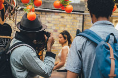 Man Wearing Grey Fedora Hat Taking Picture of Woman in White Sleeveless Top Royalty Free Stock Images