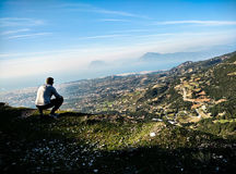 Man Wearing Grey Hoodie While Sitting on the Top of Mountain Royalty Free Stock Image
