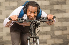 Man wearing grey office pants, white red business shirt and backpack standing by bicycle in racing position smiling. Brick wall background Stock Photo