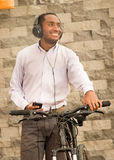 Man wearing grey office pants, white red business shirt standing by bicycle holding mobile phone, headphones on head Royalty Free Stock Photo