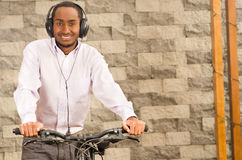 Man wearing grey office pants, white red business shirt standing by bicycle holding mobile phone, headphones on head Stock Image