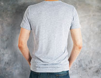 Man wearing grey shirt back. Back view of man wearing empty grey shirt on concrete background. Retail concept. Mock up Stock Photo