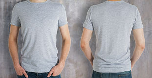 Man wearing grey shirt. Man wearing empty grey shirt on concrete background. Front and rear view. Shopping concept. Mock up Royalty Free Stock Photos