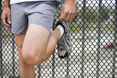 Man wearing grey shorts and trainers, leaning against wire fence, low section, close-up Royalty Free Stock Photos