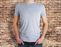 Man wearing grey t-shirt on brick background. Man wearing empty grey t-shirt on brick wall background. Advertisement and design concept. Mock up Stock Photos