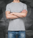 Man wearing grey t-shirt with crossed hands. Stock Photography