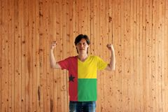 Man wearing Guinea Bissau flag color of shirt and standing with raised both fist on the wooden wall background. Vertical red line with black star two stock photography