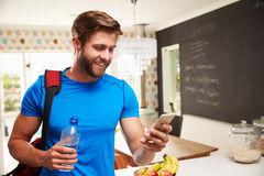 Man Wearing Gym Clothing Looking At Mobile Phone Stock Images