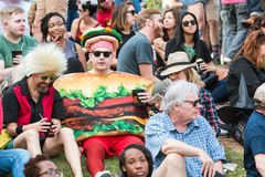 Man Wearing Hamburger Costume Awaits Start Of Atlanta Halloween Parade. Atlanta, GA, USA - October 21, 2017:  A man wearing a hamburger costume sits with a crowd Royalty Free Stock Photos