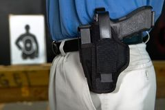 Man wearing a handgun in a webbing holster royalty free stock image