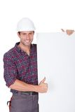 Man wearing hard hat holding placard Stock Photography