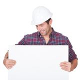 Man Wearing Hard Hat Holding Placard. On White Background Royalty Free Stock Photography