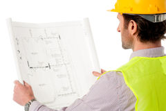 Man wearing hard hat reviewing the plan. A construction worker on the job with blueprint Royalty Free Stock Photos