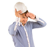 Man Wearing Hard Hat Wiping Forehead with Hand. Man in Studio Wearing Hard Hat Wiping Forehead with Back of Hand in front of White Background Royalty Free Stock Photography