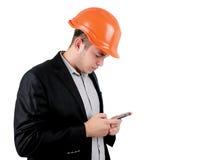 Man wearing a hardhat checking his mobile Royalty Free Stock Image