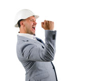 Man wearing a hardhat cheering in jubilation. And punching the air with his fist as he celebrates a success, conceptual of a builder, architect or engineer royalty free stock photo