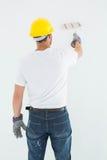 Man wearing hardhat while using paint roller Stock Image